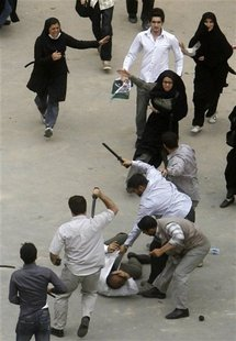 Iranian plain clothes policemen beat a demonstrator in Tehran in 2009