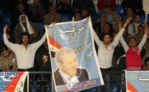 Iraqi refugees and supporters of former prime minister Iyad Allawi hold his poster during a campaign rally