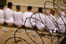 Detainees kneel during early morning Islamic prayer