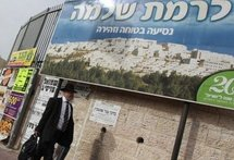 An Israeli ultra-orthodox Jewish man walks past a sign carrying the image of the east Jerusalem settlement of Ramat Shlomo on March 11. (AFP/File/Gali Tibbon)