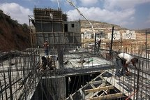 Palestinian labourers work at a construction site of new housing units in Givat Zeev Israeli settlement
