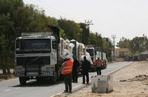 Hamas policemen inspect trucks carrying clothes and shoes as they pass the Kerem Shalom crossing on 4th April.  (AFP/File/Said Khatib)