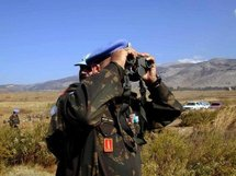 A UN officer scans the Shebaa Farms area with his binoculars.