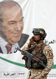 An Iraqi soldier stands in front of a portrait of former Iraqi premier Iyad Allawi in Baghdad on 17th April.