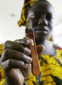 A woman who performs genital cutting shows a knife she uses during a gathering to denounce circumcision in 2005, in Abidjan.
