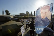 Israeli protesters stand next to a flag showing the picture of captured Israeli soldier Gilad Shalit.