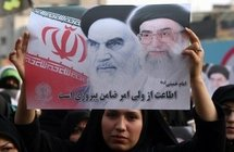A supporter of the Iranian government holding a picture of founder of the Islamic Republic Ayatollah Ruhollah Khomeni, and supreme leader Ayatollah Ali Khamenei (AFP/Atta Kenare)