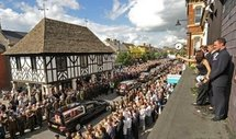 Mourners in Wootton Bassett in 2009, throwing flowers on hearses carrying the bodies of eight British soldiers killed in Afghanistan (AFP/File/Carl de Souza)
