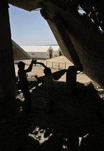 Palestinian boy plays in the shadow of a destroyed house in front of UN tents in the Jabalia refugee camp
