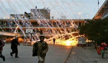 Palestinian civilians run for cover as a white phosphorous shell rains down over a UN school in Beit Lahiain, during the Israeli offensive in 2009 (AFP/File/Mohammed Abed)