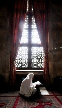 A Muslim woman reads a copy of the Qur'an (AFP/File/Adek Berry)