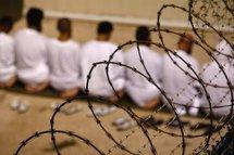 Detainees kneel during early morning Islamic prayer
