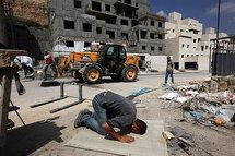 A Palestinian worker prays at the construction site in the Givat Zeev Israeli settlement in the West Bank