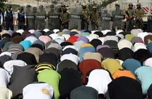 Israeli police stand guard as Palestinian Muslims perform Friday prayer outside Jerusalem's Old City