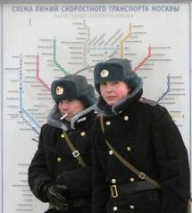 Russian policemen standing next to a map of the Moscow metro