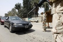 Iraqi soldiers stop vehicles at a checkpoint in Baghdad.