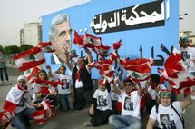 Lebanese people in front of a banner with a portrait of Rafiq Hariri.