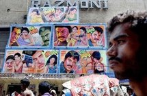A Bangladeshi man passes a wall with advertisements for screenings in Dhaka, in 2004.