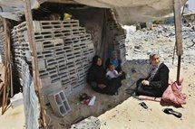 A Palestinian family sits in a makeshift shelter after its home was demolished by Hamas security forces in Rafah on 19th May.