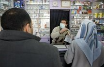 A Palestinian pharmacist serves customers in Gaza City.