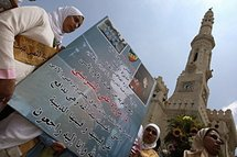 University friends of Marwa El-Sherbini march with a banner outside the Ibrahim Mosque in Alexandria.