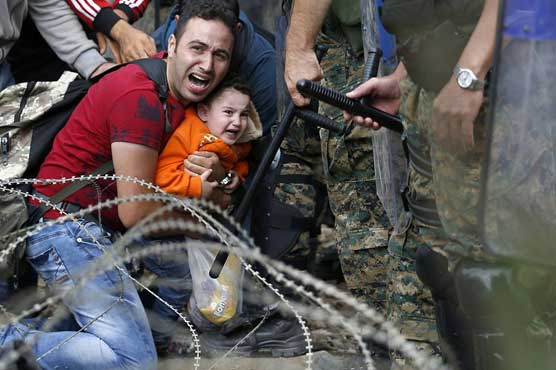 Barbed wire and stun grenades welcome refugees to Macedonia